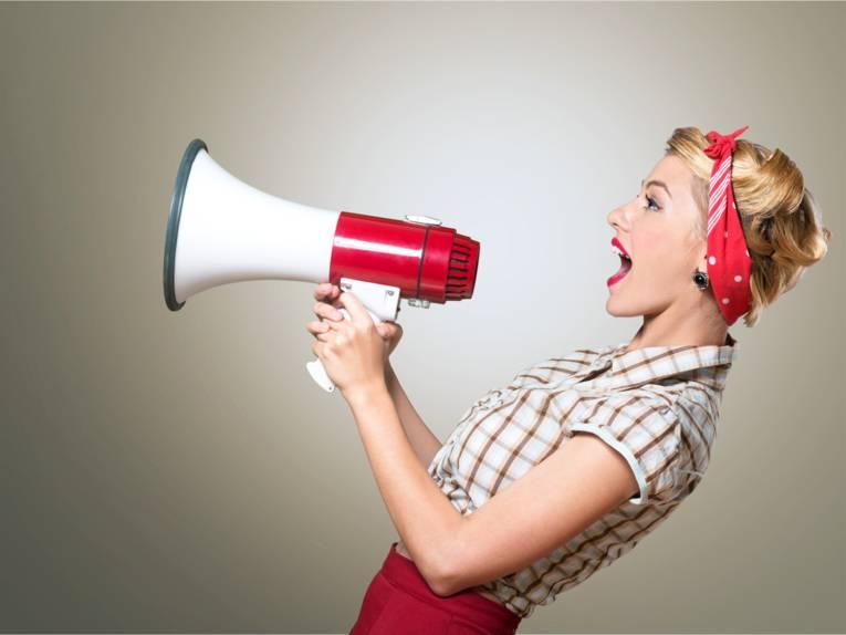 Eine Frau im Fünfziger-Jahre Look die in ein Megaphon ruft.