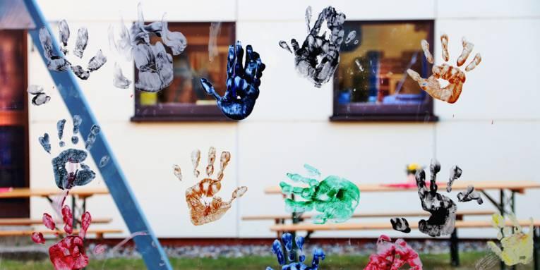 Handabdrücke in verschiedenen Farben an einer Fensterscheibe