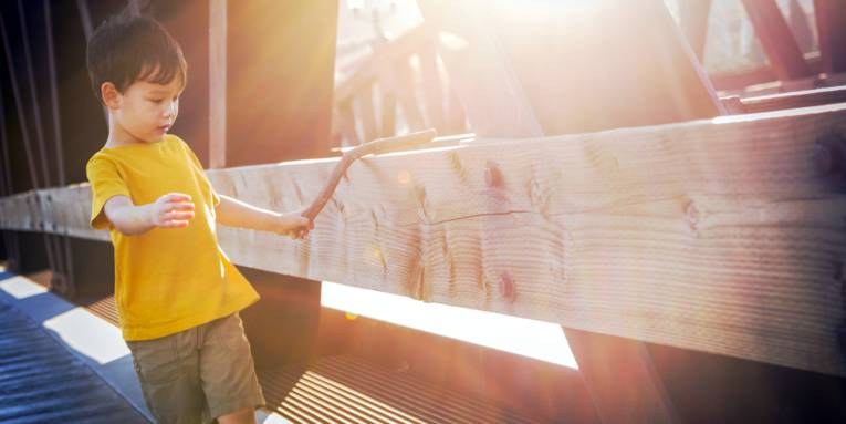 Ein Junge hat in der linken Hand einen kräftigen, kurzen, krummen Stock und führt ihn über ein Brückengeländer aus Holz. Die Sonne tauscht die Szene in warmes Licht.