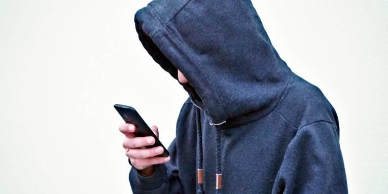 Ein Jugendlicher trägt einen Kapuzenpulli und schaut mit hängenden Schultern auf sein Smartphone.