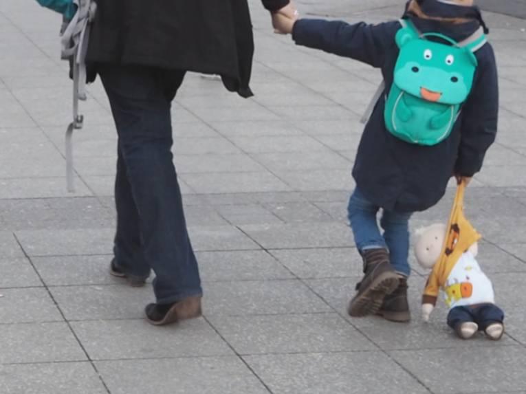Ein Kind geht neben einem Erwachsenen. Mit der linken Hand hält es die rechte Hand des Erwachsenen, mit der rechten Hand zieht es eine Stoffpuppe hinter sich her, die Puppe schleift auf dem Boden.