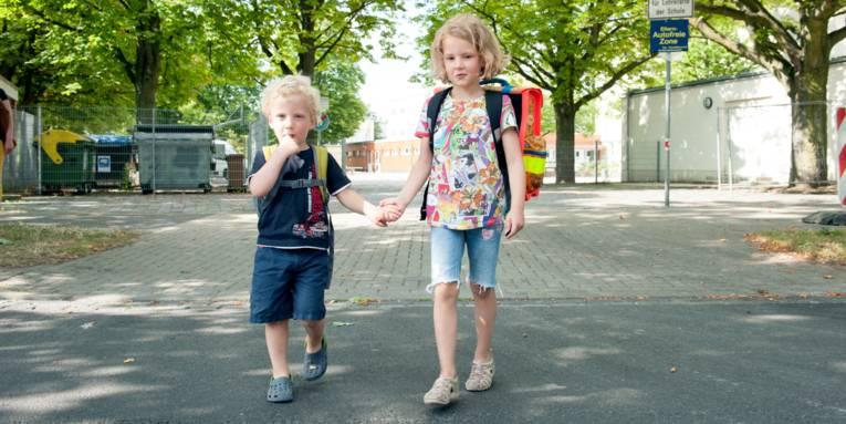 Ein Junge und ein Mädchen reichen sich die Hände und überqueren eine Straße. Kedes Kind trägt einen Schulranzen.