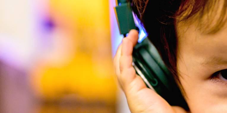 Ein Kleinkind hört über einen Kopfhörer Musik oder andere Töne.