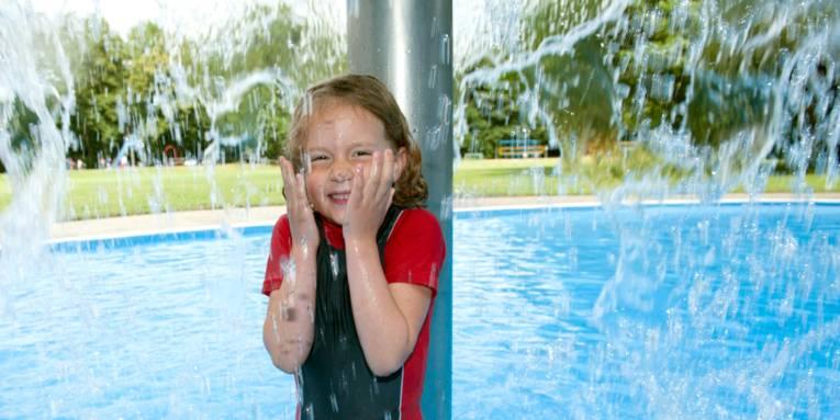 Ein Mädchen duscht im flachen Becken eines Freibades unter einem Duschpilz.