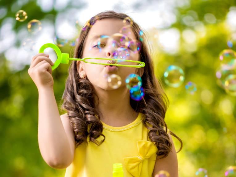 Ein Mädchen trägt ein gelbes Sommerkleid und macht Seifenblasen. Der Hintergrund ist grün.