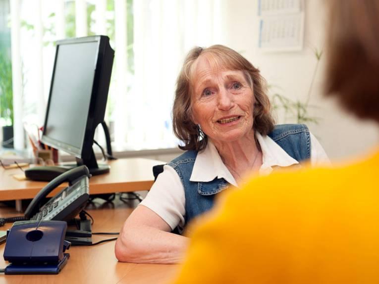 Eine ältere Frau sitzt in an einem Tisch, im Hintergrund sind ein Telefon und ein PC-Monitor zu sehen. Im Vordergrund ist unscharf der Rücken und der Kopf einer jüngeren Frau zu erkennen. Beide schauen sich an und sprechen miteinander.