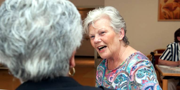 Zwei Seniorinnen sitzen beisammen und reden miteinander.