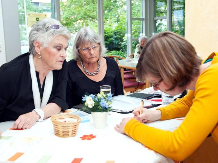 Zwei ältere Damen besprechen sich mit einer jüngeren Frau.