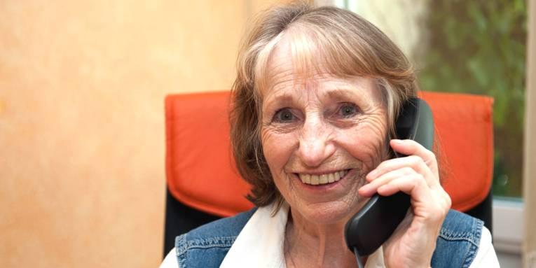 Eine ältere Dame sitzt auf einem Bürostuhl, hält einen Telefonhörer in ihrer linken Hand und lächelt in die Kamera.