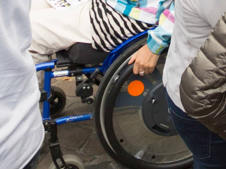 Mehrere Menschen gehen über einen Weg, eine Person fährt in einem Rollstuhl.
