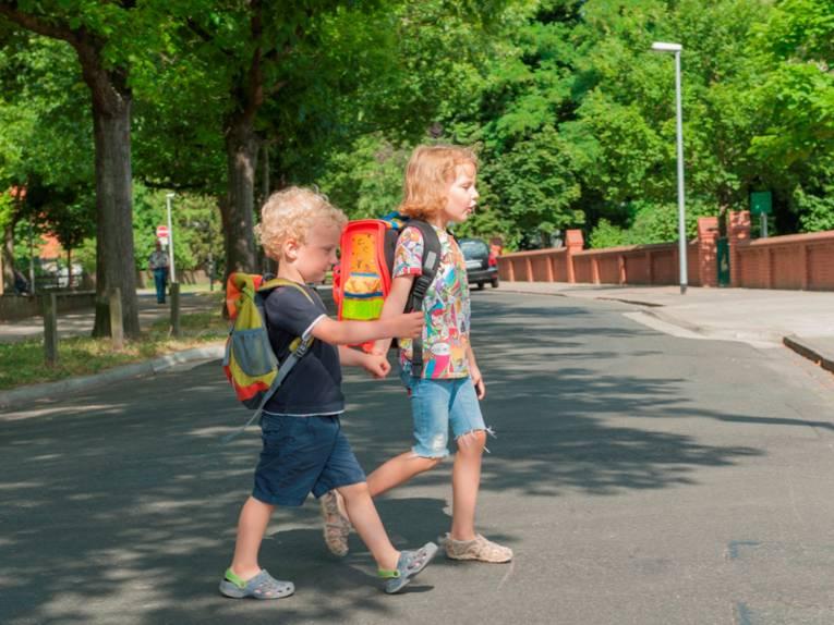 Zwei Kinder, Hand in Hand, überqueren eine Straße