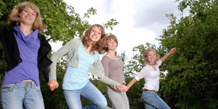 Vier strahlende junge Mädchen, die sich die Hände reichen und einen Luftsprung machen.