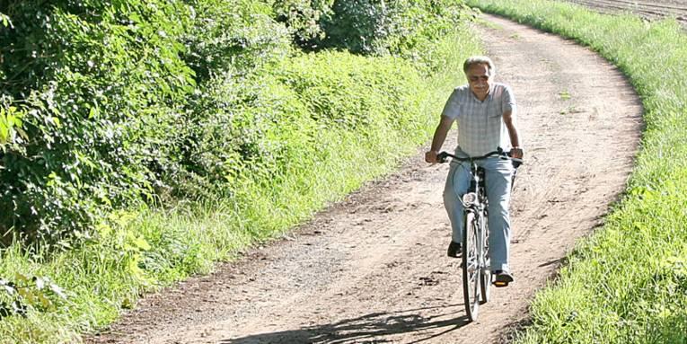 Radfahrer auf einem unbefestigten Weg im Sommer bei Sonnenschein
