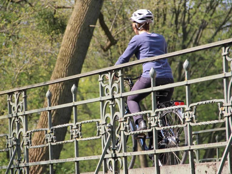 Eine Radfahrerin mit Helm im Frühling auf einer Brücke