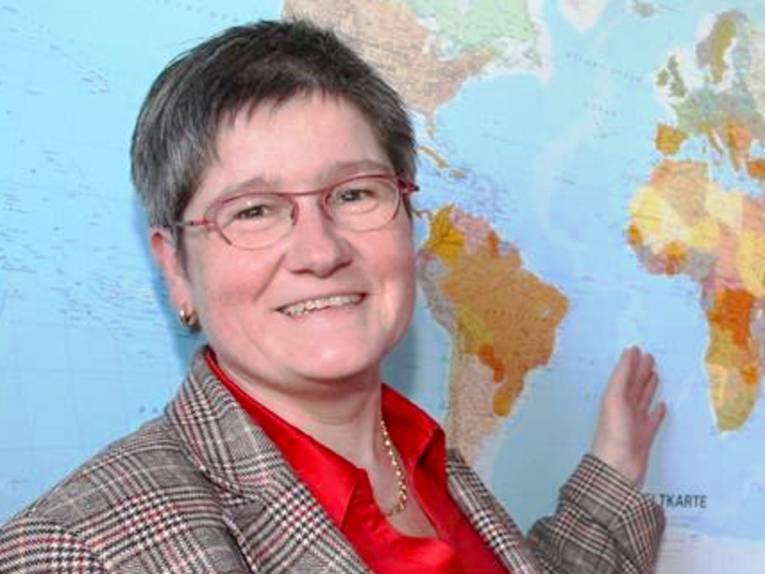 Porträtaufnahme einer Frau mit kurzen Haaren und Brille, die mit der Hand auf eine Weltkarte zeigt.