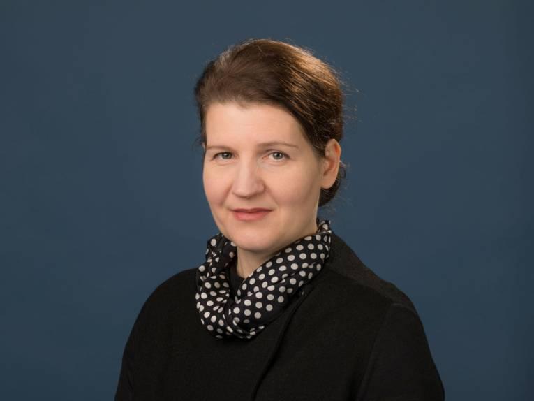 Portraitaufnahme einer Frau mit dunklem Oberteil und einem gepunktetem Halstuch.