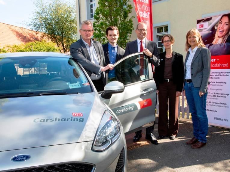 5 Personen stehen an einem silbernen Auto mit geöffneter Fahrertür.