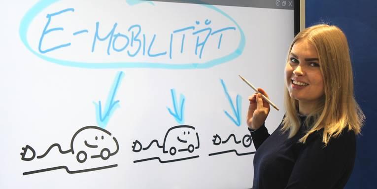 Eine Dame vor einem elektronischen Flipchart erklärt etwas zum Thema Elektromobilität