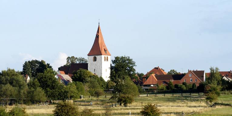 Blick über Wiesen auf den Kirchturm der St. Marienkirche von Isernhagen KB