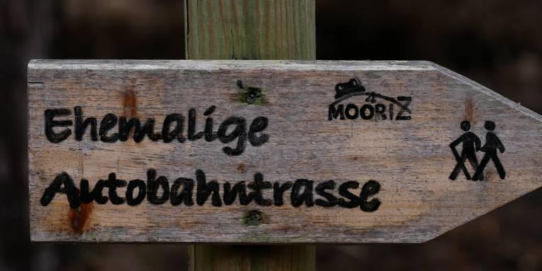 """Holzwegweiser mit der Aufschrift """"Ehemalige 'Autobahntrasse"""""""