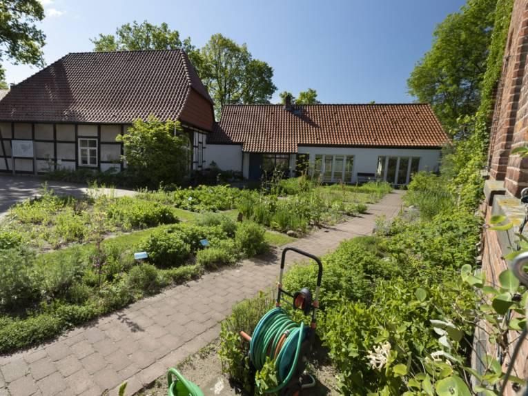 Fachwerkgebäude mit modernem Anbau, davor Beete mit Grünpflanzen