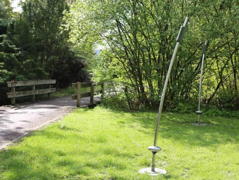 Metallstangen auf einer Rasenfläche, dahinter ein Weg und eine Brücke