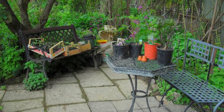 Stillleben im Garten mit Sitzgruppe und Pflanzen in Pflanzkübeln