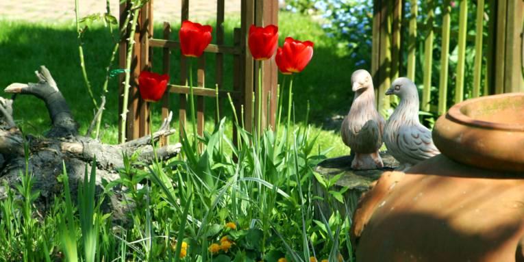 In einem Beet wachsen verschiedene Pflanzen, unter anderem rote Tulpen. Auf einem abgesägten Baumstamm stehen Tonfiguren in Taubenform.