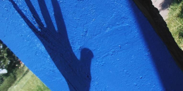 Schatten einer Hand auf einem leuchtend blauen Betonpfahl