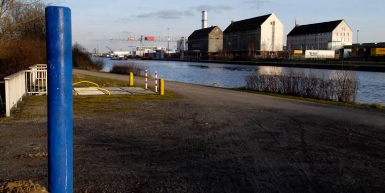 Mittellandkanal, blauer Pfahl und Weg im Vordergrund, auf der anderen Kanalseite größere Gebäude und Kräne