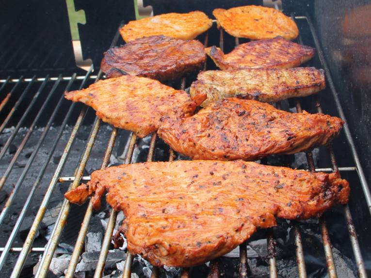 Acht Scheiben Fleisch auf einem Grillrost. Sechs Fleischstücke sind schon verzehrbereit und zwei Stücke sind noch nicht durch.