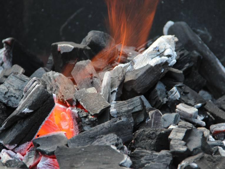 Grillkohle, die bereits entzündet ist. Es sind Glut und auch eine kleine Flamme zu sehen.