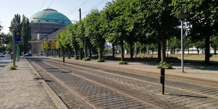 Straßenbahnschienen im Sonnenschein, im Hintergrund ein Gebäude mit Kuppel.