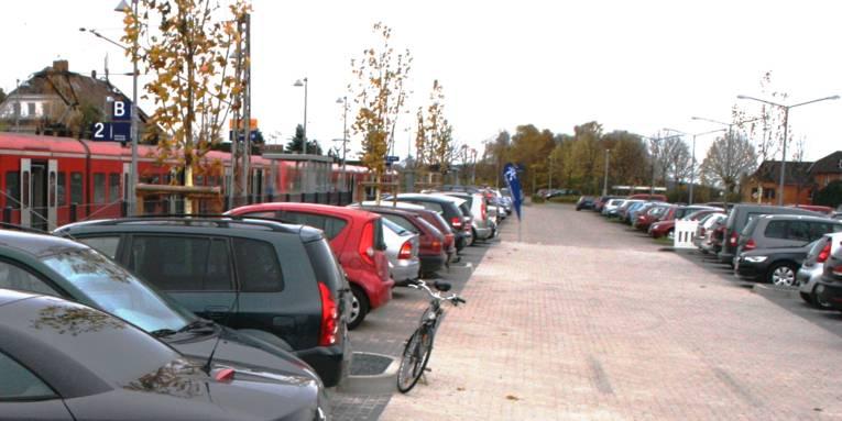 """Eine rote S-Bahn hält am Bahnsteig, die Parkbuchten davor sind mit vielen Autos und einem Fahrrad beparkt. Am Ende des Parkplatzes steht eine blaue Beachflag, bedruckt mit weißem Schriftzug """"Region Hannover"""" und dem Punktelogo der Region Hannover in weiß."""