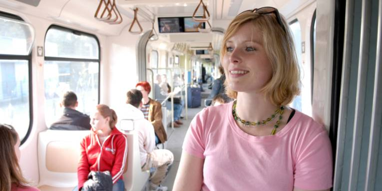 Frau mit rosa T-Shirt steht im Mittelgang einer Stadtbahn.