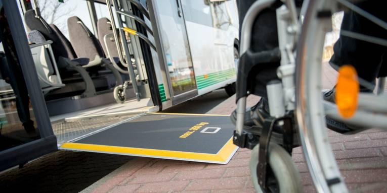 Ein Rollstuhlfahren, der sich auf die Rampe eines Linienbusses zubewegt.