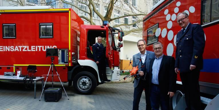 Vier Männer und zwei rote Feuerwehrfahrzeuge stehen in einem Innenhof.