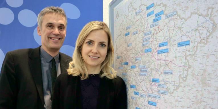 Ein Mann und eine Frau stehen vor einer Landkarte.