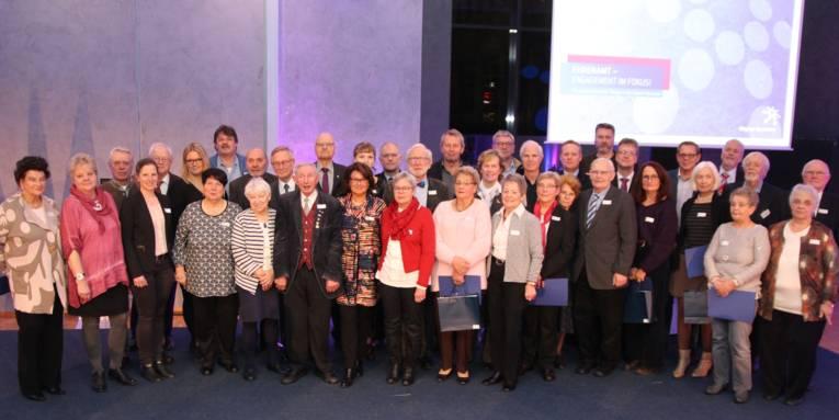Eine bunte Gruppe von fast 40 Männern und Frauen, die in einem großen Raum für das Foto im Halbkreis stehen und in die Kamera schauen.