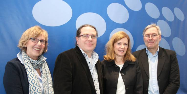 Zwei Damen und zwei Herren stehen nebeneinander in einem Raum vor einem blauen Hintergrund mit hellblauen Kreisen und lächeln in die Kamera.