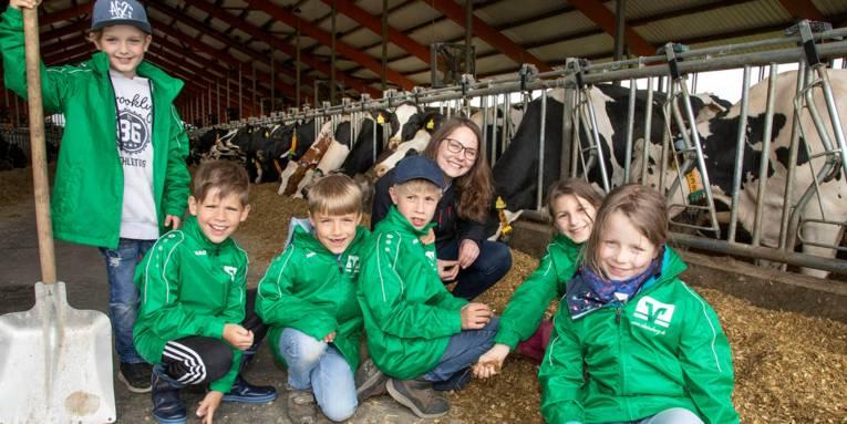 Sechs Kinder und eine Erwachsenen stehen und knien in einem Kuhstall und lachen in die Kamera.