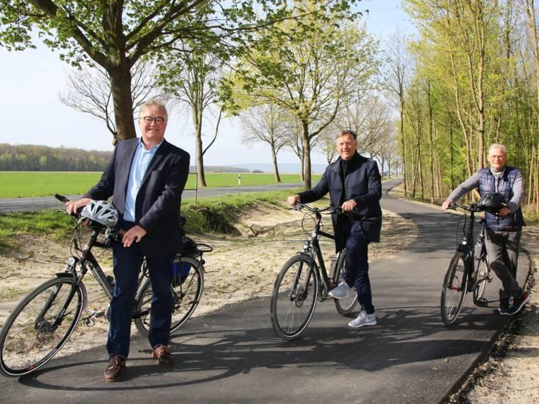 Drei Herren mit Fahrrädern auf einem neuen Radweg