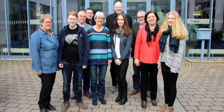 Zehn Personen haben sich für ein Gruppenfoto vor einem Schulgebäude aufgestellt.
