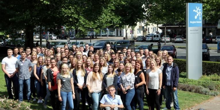 79 Personen haben sich zu einem Gruppenbild an der Hildesheimer Straße in Hannover aufgestellt. Am oberen rechten Bildrand ist das Logo der Region Hannover zu sehen.