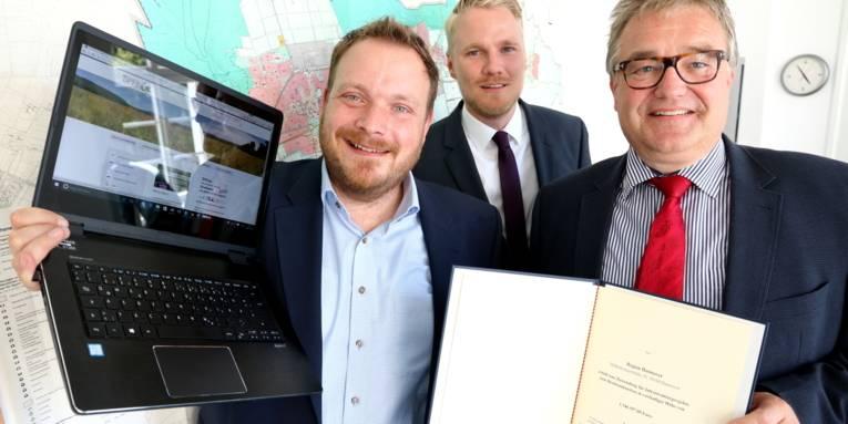 Drei Männer stehen vor einer Wandkarte, einer hat einen Laptop in den Händen, ein anderer eine Urkunde.