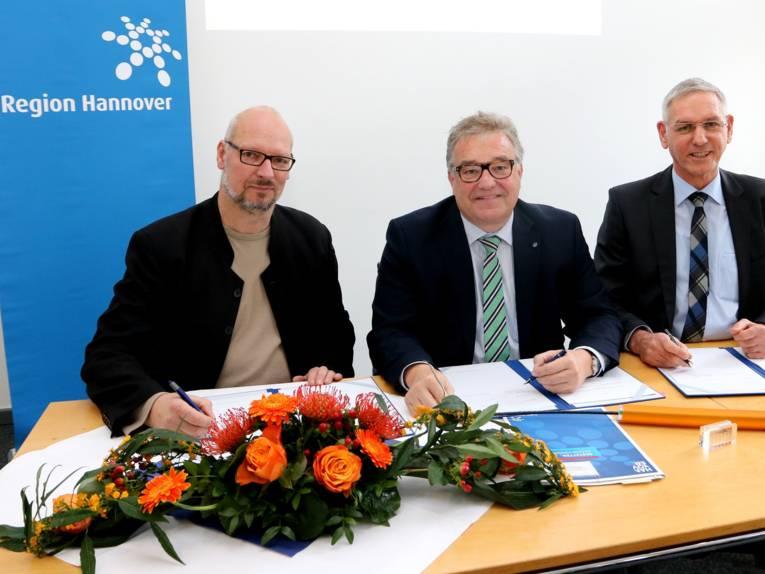 Drei Männer sitzen nebeneinander an einem Tisch und unterschreiben etwas. Auf dem Tisch sind außerdem ein Blumengebinde und ein Datenkabel.