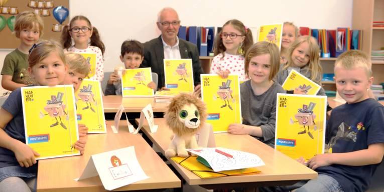 Blick in einen Unterrichtsraum, Schülerinnen und Schüler halten gelbe Mappen vor sich, ganz hinten sitzt ein Mann.