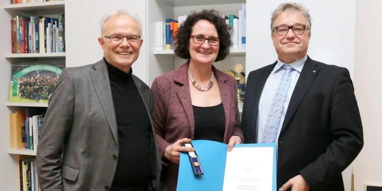 Zwei Männer stehen links und rechts einer Frau, dahinter ist ein Bücherregal. Die Frau hält eine Urkunde und eine Ehrennadel in ihren Händen.