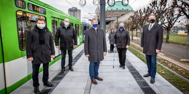 Einige Personen posieren auf einem neuen Hochbahnsteig für die Kamera. Links daneben ist eine Straßenbahn zu sehen.
