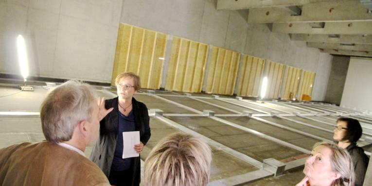 Vier Frauen und ein Mann schauen sich im Rohbau einer großen Halle um.